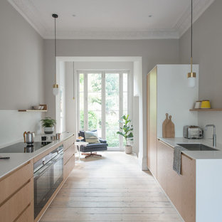 Mid-sized minimalist galley light wood floor and brown floor eat-in kitchen photo in London with white backsplash, an undermount sink, flat-panel cabinets, light wood cabinets, quartzite countertops and paneled appliances