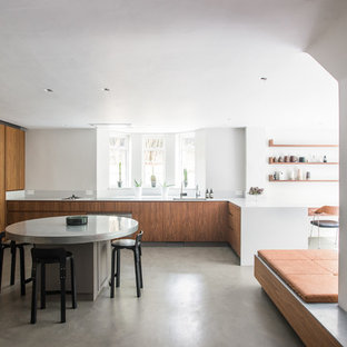 Photo of a modern u-shaped kitchen/diner in London with a submerged sink, flat-panel cabinets, medium wood cabinets, integrated appliances, concrete flooring, a breakfast bar, grey floors and white worktops.