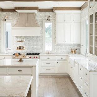 デンバーのトランジショナルスタイルのおしゃれなキッチン (エプロンフロントシンク、落し込みパネル扉のキャビネット、白いキャビネット、白いキッチンパネル、モザイクタイルのキッチンパネル、淡色無垢フローリング、ベージュの床、ベージュのキッチンカウンター) の写真