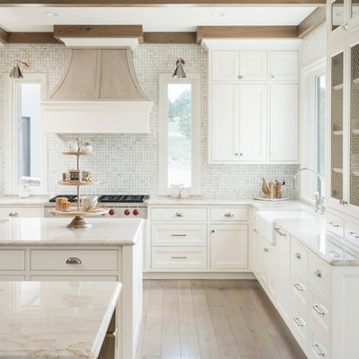 Kitchen - transitional l-shaped light wood floor and beige floor kitchen idea in Denver with a farmhouse sink, recessed-panel cabinets, white cabinets, white backsplash, mosaic tile backsplash, two islands and beige countertops