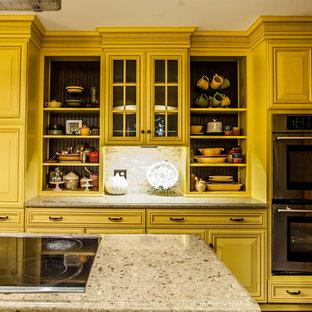 ボルチモアの中サイズのカントリー風おしゃれなキッチン (アンダーカウンターシンク、インセット扉のキャビネット、黄色いキャビネット、クオーツストーンカウンター、ベージュキッチンパネル、石タイルのキッチンパネル、シルバーの調理設備の、無垢フローリング、茶色い床) の写真
