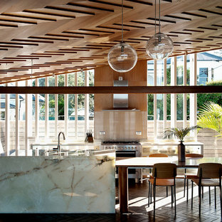 Contemporary eat-in kitchen remodeling - Example of a trendy terra-cotta floor eat-in kitchen design in Other with glass-front cabinets, glass sheet backsplash, stainless steel appliances and an island
