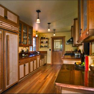 Geschlossene, Zweizeilige, Mittelgroße Asiatische Küche ohne Insel mit Landhausspüle, flächenbündigen Schrankfronten, hellen Holzschränken, Kupfer-Arbeitsplatte, Elektrogeräten mit Frontblende und braunem Holzboden in Santa Barbara