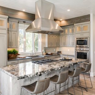 Photo of a country l-shaped kitchen in Boise with a farmhouse sink, recessed-panel cabinets, beige cabinets, beige splashback, stainless steel appliances, light hardwood floors, with island, multi-coloured benchtop and granite benchtops.