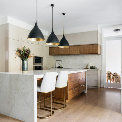 Kitchen - contemporary u-shaped medium tone wood floor and brown floor kitchen idea in Chicago with flat-panel cabinets, gray cabinets, stainless steel appliances, an island and white countertops