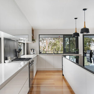 Mid-sized contemporary l-shaped eat-in kitchen in Hobart with a drop-in sink, white cabinets, laminate benchtops, laminate floors, with island, flat-panel cabinets, black splashback, black appliances, brown floor and white benchtop.