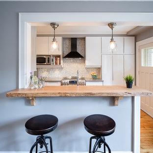 オタワの小さいトランジショナルスタイルのおしゃれなキッチン (ドロップインシンク、フラットパネル扉のキャビネット、白いキャビネット、コンクリートカウンター、グレーのキッチンパネル、石タイルのキッチンパネル、シルバーの調理設備、無垢フローリング) の写真
