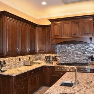 ジャクソンビルの大きいエクレクティックスタイルのおしゃれなキッチン (アンダーカウンターシンク、レイズドパネル扉のキャビネット、濃色木目調キャビネット、御影石カウンター、メタリックのキッチンパネル、ボーダータイルのキッチンパネル、シルバーの調理設備の、磁器タイルの床) の写真