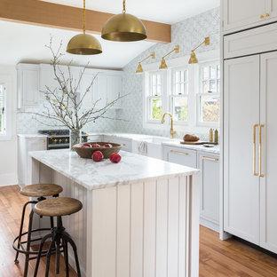 Foto på ett vintage l-kök, med en rustik diskho, skåp i shakerstil, grå skåp, blått stänkskydd, svarta vitvaror, mellanmörkt trägolv och en köksö