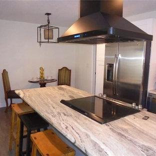 タンパのシャビーシック調のおしゃれなキッチン (ドロップインシンク、シェーカースタイル扉のキャビネット、白いキャビネット、御影石カウンター、グレーのキッチンパネル、サブウェイタイルのキッチンパネル、シルバーの調理設備、ラミネートの床、緑の床) の写真