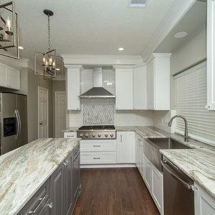 ヒューストンの大きいシャビーシック調のおしゃれなキッチン (エプロンフロントシンク、レイズドパネル扉のキャビネット、白いキャビネット、御影石カウンター、白いキッチンパネル、サブウェイタイルのキッチンパネル、シルバーの調理設備の、磁器タイルの床、茶色い床、グレーのキッチンカウンター) の写真