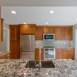 マイアミのトラディショナルスタイルのおしゃれなキッチン (エプロンフロントシンク、ルーバー扉のキャビネット、中間色木目調キャビネット、御影石カウンター、青いキッチンパネル、ガラス板のキッチンパネル、シルバーの調理設備) の写真