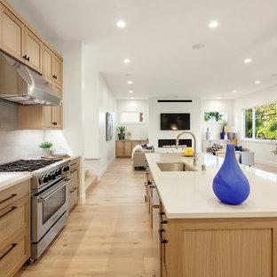 На фото: угловая кухня-гостиная в стиле современная классика с врезной раковиной, фасадами в стиле шейкер, фасадами цвета дерева среднего тона, светлым паркетным полом, островом, бежевым полом и белой столешницей