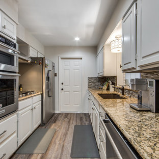 Small midcentury galley separate kitchen in Austin with a drop-in sink, beaded inset cabinets, white cabinets, granite benchtops, grey splashback, glass tile splashback, stainless steel appliances, vinyl floors, with island, grey floor and beige benchtop.