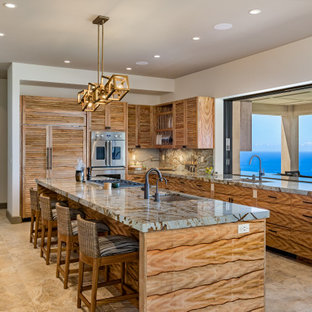 Inspiration for a tropical u-shaped kitchen in Hawaii with an undermount sink, louvered cabinets, medium wood cabinets, with island, beige floor and grey benchtop.