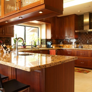 Design ideas for a mid-sized tropical u-shaped kitchen in Hawaii with an undermount sink, shaker cabinets, dark wood cabinets, granite benchtops, yellow splashback, stone slab splashback, stainless steel appliances, ceramic floors and a peninsula.