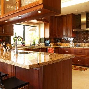 Foto på ett mellanstort tropiskt u-kök, med en undermonterad diskho, skåp i shakerstil, skåp i mörkt trä, granitbänkskiva, gult stänkskydd, stänkskydd i sten, rostfria vitvaror, klinkergolv i keramik och en halv köksö