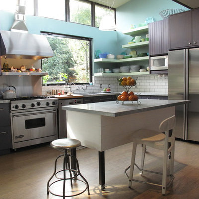 Large trendy l-shaped light wood floor eat-in kitchen photo in San Francisco with stainless steel appliances, flat-panel cabinets, marble countertops, white backsplash, subway tile backsplash, an undermount sink, an island and purple cabinets