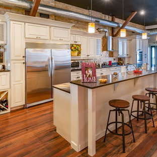 Inspiration for an industrial galley open plan kitchen in Grand Rapids with raised-panel cabinets, white cabinets, stainless steel appliances, medium hardwood floors and with island.