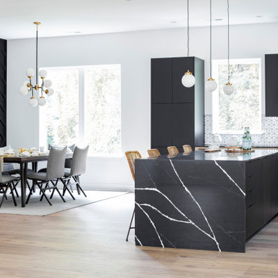 Example of a trendy kitchen design in Charlotte with flat-panel cabinets, black cabinets, quartz countertops, white backsplash, an island and black countertops
