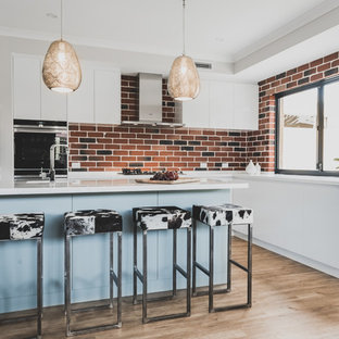 Design ideas for a contemporary l-shaped kitchen in Perth with brick splashback, with island, white benchtop, flat-panel cabinets, white cabinets, red splashback and brown floor.