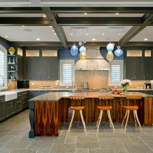 Foto de cocina en U con fregadero sobremueble, armarios con paneles lisos, puertas de armario marrones, salpicadero multicolor, electrodomésticos de acero inoxidable, una isla y suelo gris