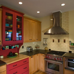 Traditional kitchen designs - Example of a classic kitchen design in Other with subway tile backsplash, concrete countertops, red cabinets and stainless steel appliances