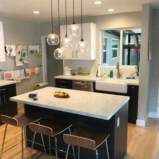 ロサンゼルスの大きいコンテンポラリースタイルのおしゃれなキッチン (エプロンフロントシンク、フラットパネル扉のキャビネット、濃色木目調キャビネット、珪岩カウンター、サブウェイタイルのキッチンパネル、シルバーの調理設備の、淡色無垢フローリング、黄色い床、白いキッチンパネル、白いキッチンカウンター) の写真