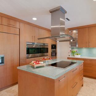 マイアミのコンテンポラリースタイルのおしゃれなキッチン (フラットパネル扉のキャビネット、ガラスカウンター、中間色木目調キャビネット、パネルと同色の調理設備、ターコイズのキッチンカウンター) の写真