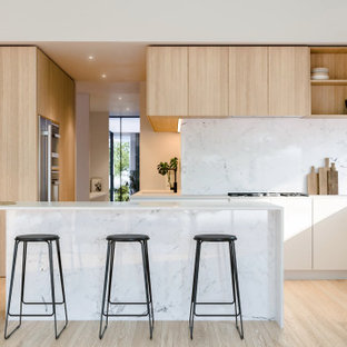 Mid-sized contemporary galley open plan kitchen in Perth with an undermount sink, flat-panel cabinets, white cabinets, marble benchtops, white splashback, marble splashback, stainless steel appliances, light hardwood floors, with island, brown floor and white benchtop.
