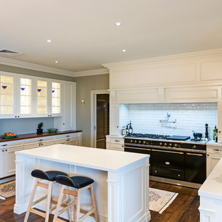 Design ideas for a transitional u-shaped eat-in kitchen in Melbourne with a farmhouse sink, recessed-panel cabinets, white cabinets, white splashback, subway tile splashback, black appliances, dark hardwood floors, with island, brown floor and white benchtop.