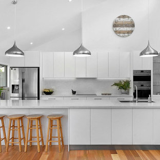 Inspiration for a contemporary galley kitchen in Sydney with an undermount sink, flat-panel cabinets, white cabinets, grey splashback, stainless steel appliances, medium hardwood floors, with island, brown floor, grey benchtop and vaulted.