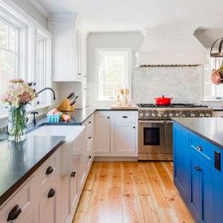 Diseño de cocina en L, tradicional, de tamaño medio, con armarios estilo shaker, puertas de armario blancas, encimera de granito, salpicadero de azulejos de porcelana, electrodomésticos de acero inoxidable, suelo de linóleo, una isla, fregadero sobremueble y suelo naranja