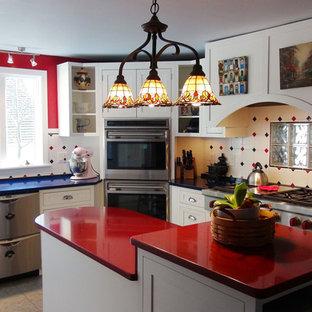 ポートランド(メイン)の中サイズのエクレクティックスタイルのおしゃれなキッチン (シェーカースタイル扉のキャビネット、白いキャビネット、人工大理石カウンター、マルチカラーのキッチンパネル、セラミックタイルのキッチンパネル、シルバーの調理設備の、セラミックタイルの床、マルチカラーの床、青いキッチンカウンター) の写真