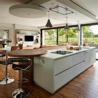 Design ideas for a medium sized contemporary open plan kitchen in Buckinghamshire with a submerged sink, flat-panel cabinets, dark hardwood flooring, an island, brown floors, beige worktops and white cabinets.