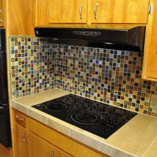 サクラメントの中くらいのエクレクティックスタイルのおしゃれなキッチン (アンダーカウンターシンク、フラットパネル扉のキャビネット、中間色木目調キャビネット、タイルカウンター、マルチカラーのキッチンパネル、磁器タイルのキッチンパネル、黒い調理設備、ライムストーンの床、マルチカラーの床) の写真