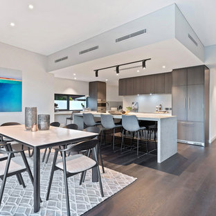 This is an example of a contemporary l-shaped eat-in kitchen in Perth with flat-panel cabinets, brown cabinets, white splashback, window splashback, panelled appliances, dark hardwood floors, with island, brown floor and white benchtop.