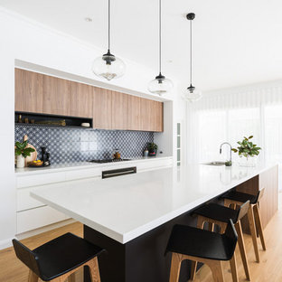 Contemporary kitchen in Perth with an undermount sink, flat-panel cabinets, light wood cabinets, multi-coloured splashback, light hardwood floors, with island and white benchtop.