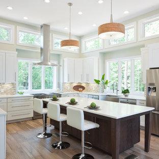 На фото: огромная п-образная кухня в стиле современная классика с раковиной в стиле кантри, фасадами в стиле шейкер, белыми фасадами, столешницей из кварцевого агломерата, бежевым фартуком, фартуком из стеклянной плитки, техникой из нержавеющей стали, полом из керамогранита, островом, обеденным столом, бежевым полом и белой столешницей с