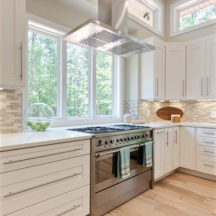 This is an example of an expansive contemporary u-shaped eat-in kitchen in Atlanta with a farmhouse sink, shaker cabinets, white cabinets, quartz benchtops, beige splashback, glass tile splashback, stainless steel appliances, porcelain floors, with island, beige floor and white benchtop.