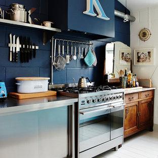 ロンドンの広いおしゃれなキッチン (エプロンフロントシンク、フラットパネル扉のキャビネット、青いキャビネット、タイルカウンター、シルバーの調理設備、塗装フローリング、白い床、グレーのキッチンカウンター) の写真