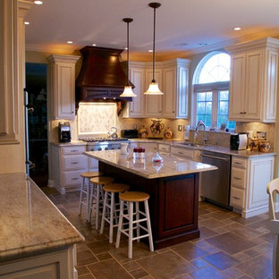 Inspiration for a large timeless l-shaped travertine floor eat-in kitchen remodel in Philadelphia with an undermount sink, granite countertops, beige backsplash, stainless steel appliances, raised-panel cabinets, white cabinets and an island