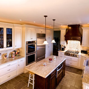Large elegant l-shaped travertine floor eat-in kitchen photo in Philadelphia with an undermount sink, granite countertops, stainless steel appliances, raised-panel cabinets, white cabinets, beige backsplash and an island