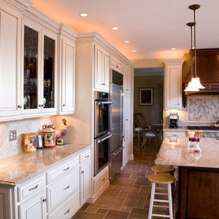 Large elegant l-shaped travertine floor eat-in kitchen photo in Philadelphia with an undermount sink, granite countertops, beige backsplash, stainless steel appliances, raised-panel cabinets, white cabinets and an island