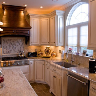 Example of a large classic l-shaped travertine floor eat-in kitchen design in Philadelphia with an undermount sink, granite countertops, stainless steel appliances, raised-panel cabinets, white cabinets, beige backsplash and an island