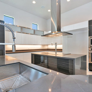 Photo of a large contemporary l-shaped open plan kitchen in Miami with an undermount sink, flat-panel cabinets, white cabinets, concrete benchtops, beige splashback, stainless steel appliances, marble floors, multiple islands and white floor.