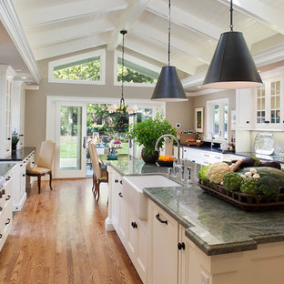 Example of a classic galley medium tone wood floor eat-in kitchen design in San Francisco with a farmhouse sink, recessed-panel cabinets, white cabinets, stainless steel appliances and an island