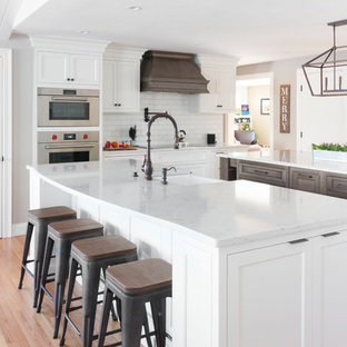 Inspiration for a country u-shaped kitchen in Boston with a farmhouse sink, shaker cabinets, white cabinets, white splashback, subway tile splashback, stainless steel appliances, light hardwood floors, multiple islands, beige floor and white benchtop.