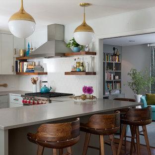 Mittelgroße Moderne Küche in L-Form mit flächenbündigen Schrankfronten, grauen Schränken, Küchenrückwand in Weiß, Halbinsel, Unterbauwaschbecken, Quarzwerkstein-Arbeitsplatte, Rückwand aus Mosaikfliesen, Küchengeräten aus Edelstahl, dunklem Holzboden, braunem Boden und grauer Arbeitsplatte in Austin