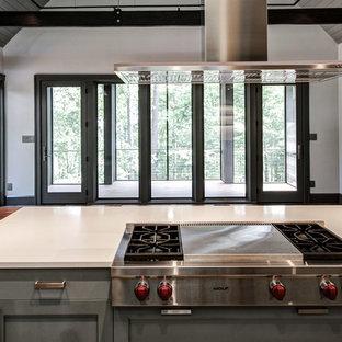 Große Moderne Wohnküche in U-Form mit Landhausspüle, Schrankfronten im Shaker-Stil, blauen Schränken, Mineralwerkstoff-Arbeitsplatte, Küchenrückwand in Weiß, Glasrückwand, Küchengeräten aus Edelstahl, Porzellan-Bodenfliesen und Kücheninsel in Sonstige
